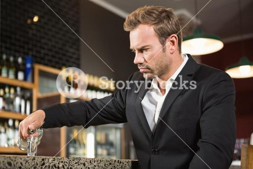 Tired man pouring a shot of alcohol