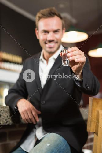 Handsome man having a shot of alcohol