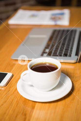 View of coffee, laptop, smartphone and newspaper