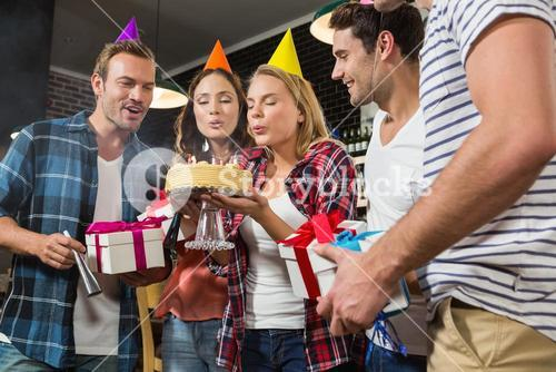 Cute woman blowing her birthday candles with a group of friends