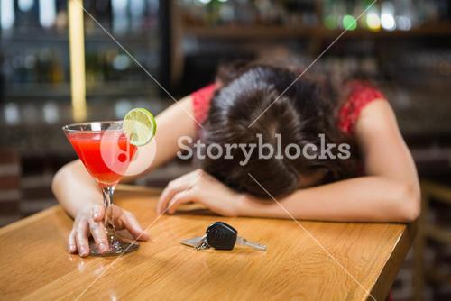 Drunk woman driver leaning on counter with her cocktail