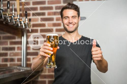 Handsome man holding a pint of beer with thumbs up