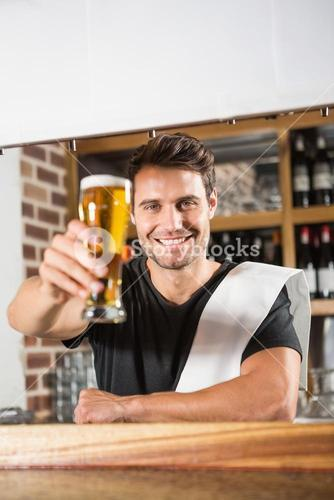 Handsome barman holding a pint of beer