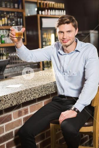 Handsome man holding a glass of whiskey