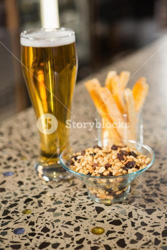 view of aperitif snacks on counter and pint of beer