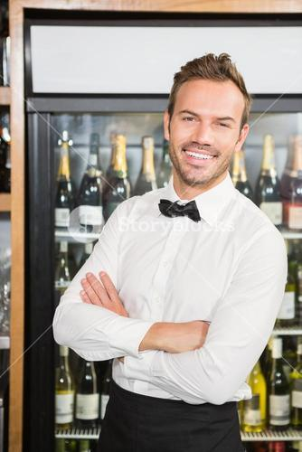 Handsome barman with arms folded