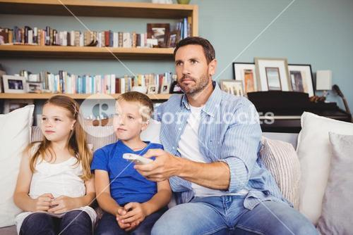 Family watching television while sitting on sofa