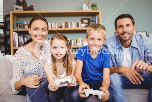 Smiling children playing video games with parents