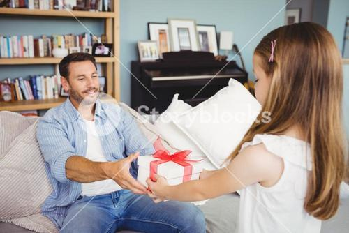 Daughter giving gift to father