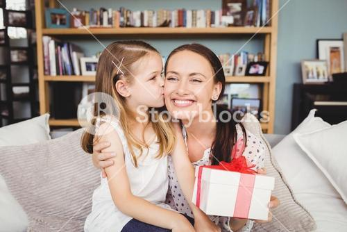 Daughter kissing mother with gift box
