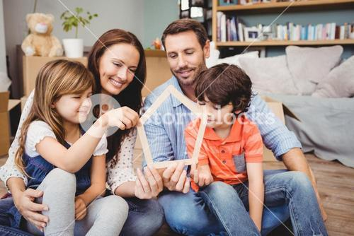 Smiling family holding house shape at home
