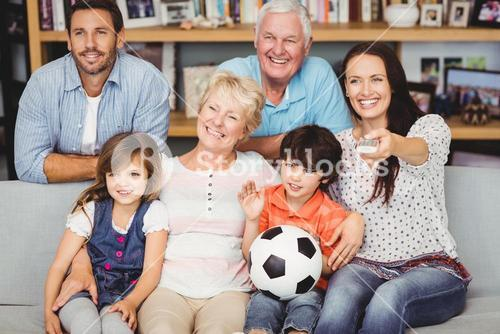 Smiling family watching football match