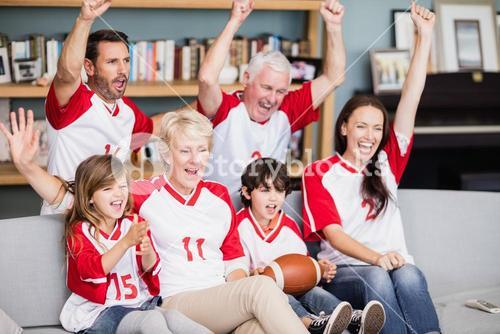 Smiling family with grandparents watching American football match