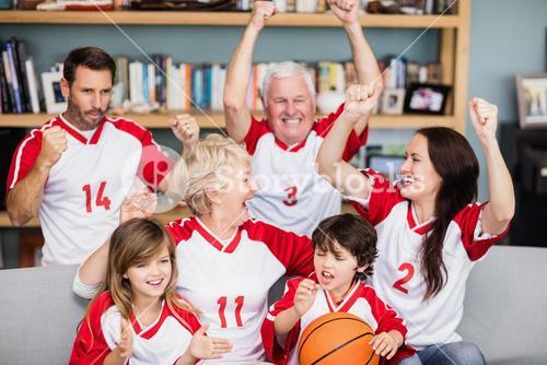 Happy family with grandparents watching basketball match