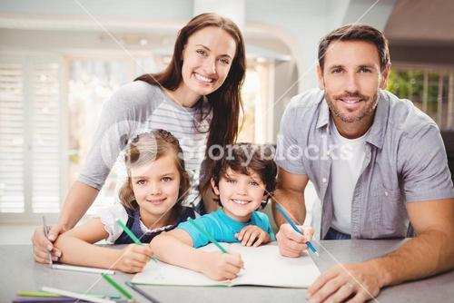 Portrait of smiling family writing in book