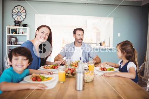 Smiling family with food on dining table