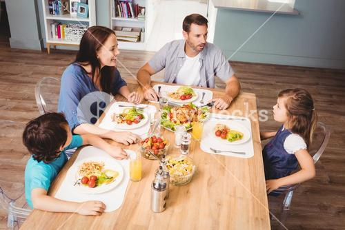 Family discussing with food on dining table