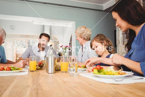 Family with grandparents sitting at dining table