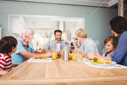 Family with grandparents discussing at dining table