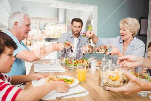Granny giving food to granddad while sitting at dining table