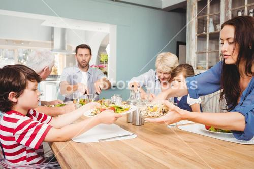 Mother giving food to son while sitting at dining table