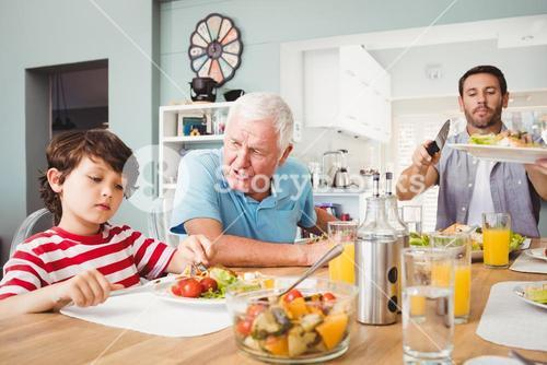 Granddad talking to grandson while sitting at dining table