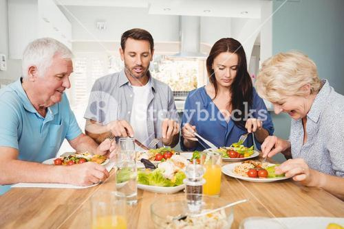 Family sitting at dining table with food