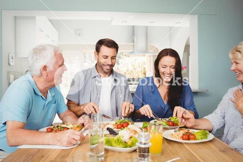 Family laughing while sitting at dining table