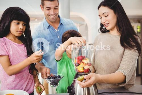 Happy family preparing fruit juice