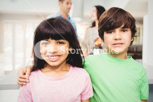 Portrait of smiling siblings standing at table