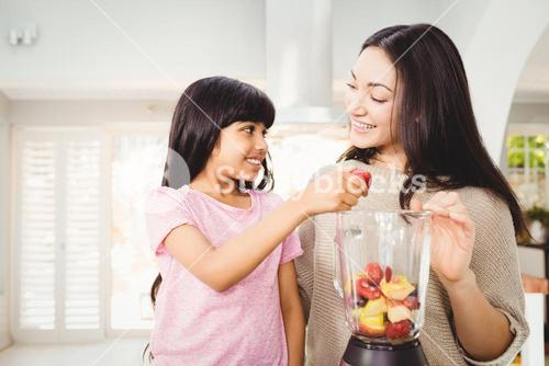 Mother and daughter preparing fruit juice