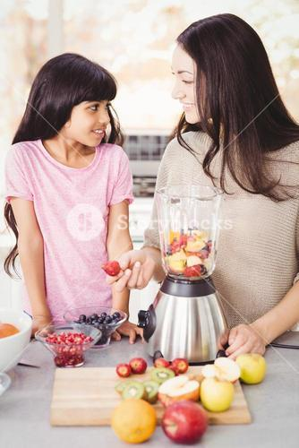 Cheerful mother and daughter preparing fruit juice