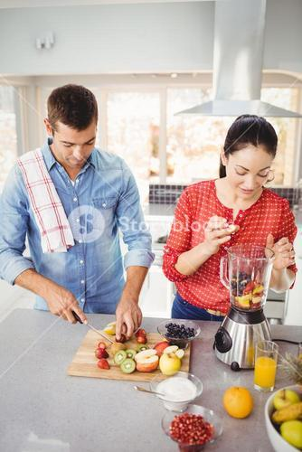 Couple preparing fruit juice