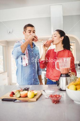 Smiling couple drinking fruit juice