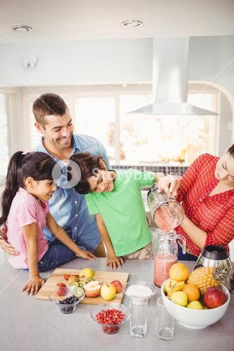 Cheerful family with mother pouring fruit juice in jug