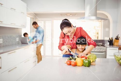 Woman teaching daughter to cut vegetables at table