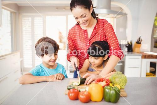 Woman chopping vegetables while children standing by table