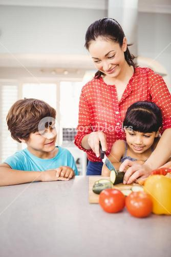 Happy children looking at mother chopping vegetables