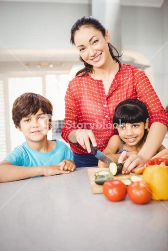 Woman standing with children by table while chopping vegetable