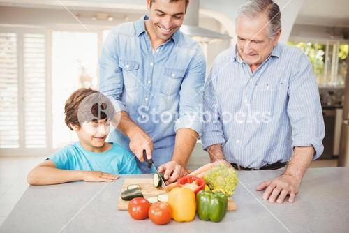 Man chopping vegetable with son and father