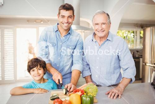 Happy man chopping vegetables with son and father