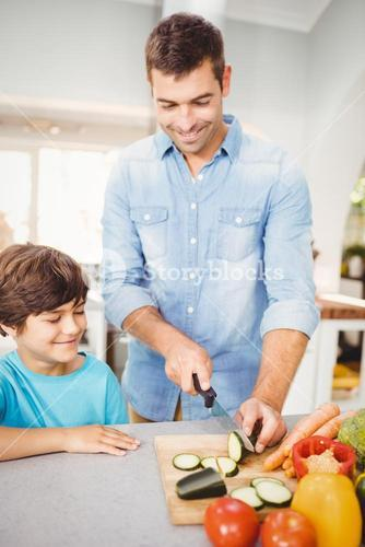 Happy man chopping vegetable with son