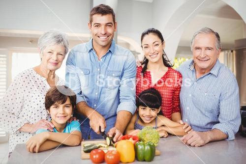 Portrait of happy family by kitchen table