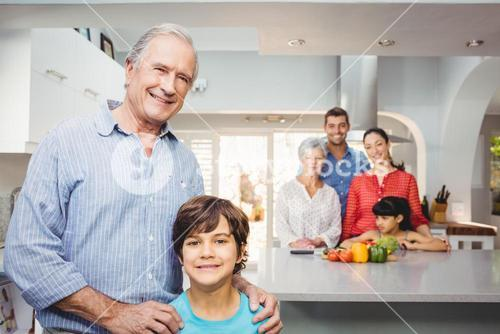 Boy with grandfather while family by kitchen table in background