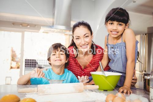 Happy woman with children preparing food at home