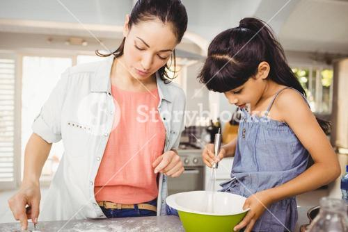 Close-up of woman preparing food with daughter