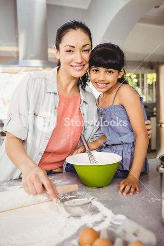 Portrait of cheerful woman preparing food with daughter