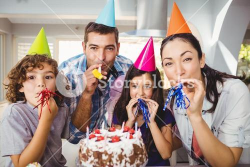 Happy family blowing party horn during birthday celebration