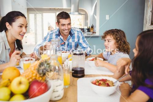 Cheerful family eating breakfast at table