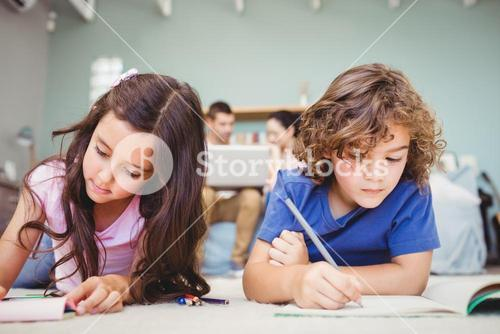 Children studying while parents in background